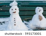 Two Snowmen On A City Bench