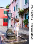 Small photo of Girl looks at fountain. First acquaintance with fountains of island of Burano.