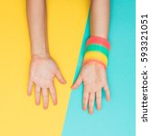 Small photo of hands palms up and with the rainbow bracelet in the style of the 90s. minimalism and fashion.