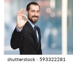 Small photo of Smiling businessman making alright sign