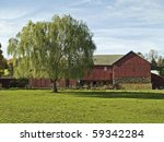 A rural Bucks County Pennsylvania scene with a weeping willow tree and an old red barn. - stock photo