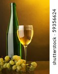 a glass of white wine bottle and green grape - stock photo