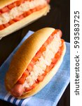 Small photo of Chilean Completo Clasico (classical) or Aleman (German) traditional hot dog sandwich with tomato and sauerkraut, photographed with natural light (Selective Focus one third into the hotdog)