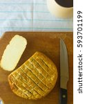 Small photo of cut head of traditional Adygei cheese handmade with knife and a Cup of coffee on wooden Board