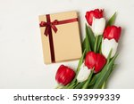 Small photo of Red and white tulips on a light background with a gift. Concept of spring, Women's Day, Mother's Day, 8 March, the holiday greetings. Place for your text