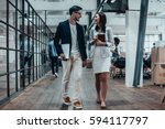 Small photo of Mutual understanding. Full length of two young colleagues in smart casual wear discussing business and smiling while walking through the large modern office