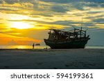 Small photo of SHIPWRECK AGROUND ON SAND BANK , UNIDENTIFIED TOURIST WALKING PASSED , WONDERFUL COLORFUL TWILIGHT SKY CLOUD BACKGROUND