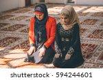 muslim women kneeling in prayer | Shutterstock . vector #594244601