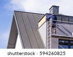 roofer assembles sheet metal on ... | Shutterstock . vector #594260825