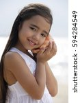 Small photo of Young girl on beach holding conk shell to her ear, smiling