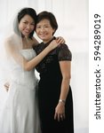 a bride and her mother smile at ... | Shutterstock . vector #594289019