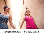 Small photo of Portrait of student friends walking visiting picturesque narrow city street with fun expressions on school trip holiday, sunny outdoors. Adolescent women enjoying travel lifestyle together, exterior.