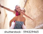Small photo of Student girls friends joyful smiling looking at camera, playful carrying piggy back, in picturesque city street monument, school trip holiday outdoors. Adolescent women travel lifestyle together.