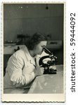 Vintage photo of young female doctor with microscope (early fifties) - stock photo