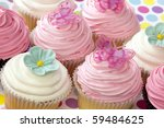 Lots of fancy cupcakes.  Frosted in pink and white, and topped with flowers and butterflies.  Pastel tones. - stock photo