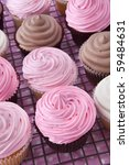Lots of cupcakes on a cooling rack.  Iced with pink, white, and chocolate frosting. - stock photo