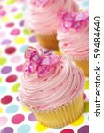 Vanilla cupcakes with pink frosting and glittery butterflies, over polka dot background.  Fun! - stock photo