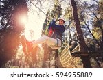 Small photo of Happy school girl enjoying activity in a climbing adventure park on a summer day