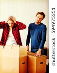 Small photo of Couple unpaking boxes, woman looking to inside and aghast holding her head