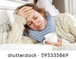 sick woman with cup of tea.... | Shutterstock . vector #595335869