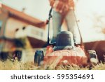 man cutting grass in his yard... | Shutterstock . vector #595354691