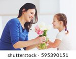 happy daughter giving mother a... | Shutterstock . vector #595390151