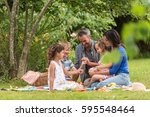 cheerful family sitting on the... | Shutterstock . vector #595548464