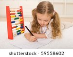 Back to school theme - little girl refreshing the knowledge forgotten over summer - stock photo