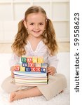 Happy little girl ready to go back to school - smiling while sitting with lots of books - stock photo