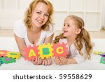 Little girl preparing for school playing and learning at home with her mother - stock photo