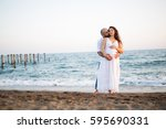 happy young pregnant couple... | Shutterstock . vector #595690331