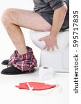 Small photo of Man sitting on a toilet with enema bag