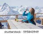 a woman snowboarder drinking... | Shutterstock . vector #595843949