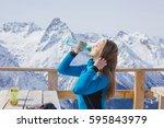a woman snowboarder drinking... | Shutterstock . vector #595843979