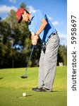 male golfer in putting green about to put the ball in the hole - stock photo