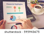 Small photo of Chief financial officer or CFO holds, sees and analyses financial highlights on his table. Financial highlights include charts of total sales revenue and sales revenue breakdown by geography or region