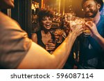 group of young people toasting... | Shutterstock . vector #596087114