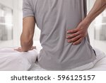 man suffering from back pain at ...   Shutterstock . vector #596125157