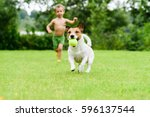 Stock photo dog with ball running from child playing catch up game 596137544