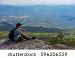 the trekker is sitting on the... | Shutterstock . vector #596206529