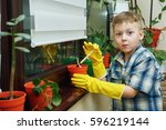 the boy takes care of flowers... | Shutterstock . vector #596219144