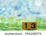 Stock photo number thirteen made by wooden block on blurred glitter background 596248574