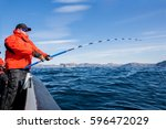 man pulls out of sea fish.... | Shutterstock . vector #596472029