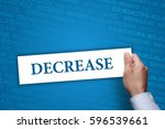 Small photo of Businessman holding Decrease sing