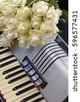 Small photo of Vintage accordion and a bouquet of white roses. Concept of a nostalgic music. Still life with a traditional folk musical instrument.
