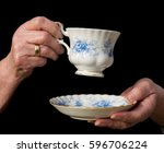 teacup and saucer held in an... | Shutterstock . vector #596706224