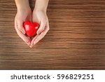 female hands holding red heart...   Shutterstock . vector #596829251