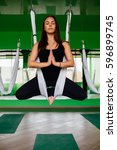 Small photo of portrait young women making antigravity yoga exercises. Aerial aero fly fitness trainer workout. white hammocks, eco green background studio. lotus. meditates. harmony and serenity concept