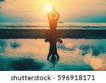 sunset yoga woman on sea coast. | Shutterstock . vector #596918171