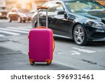 Small photo of Luggage bag on the city street ready to pick by airport transfer taxi car.